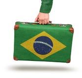 Male hand holding vintage Brazilian flag suitcase Stock Image