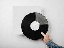 Male hand holding vinyl music album template on Stock Photos