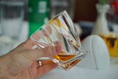 Male hand holding a whiskey glass with golden liquor as a symbol of drinking alcohol Royalty Free Stock Photos