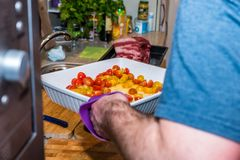 Male hand holding white ceramic baking tray with chopped tomatoes over raw beef roast kitchen table.  Royalty Free Stock Photos