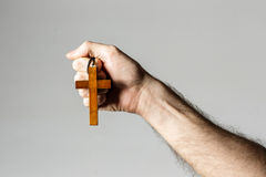 Male hand holding wooden cross Stock Photos