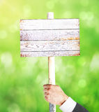 Male hand holding wooden signboard. Businessman hand holding empty wooden signboard on green background. Mock up, 3D Rendering Royalty Free Stock Images