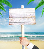Male hand holding wooden signboard. Businessman hand holding empty wooden signboard on seashore background. Mock up, 3D Rendering Stock Photography