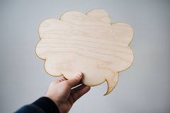 Male hand holding wooden thoughts cloud Stock Photo