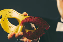 Male hand holds carnival mask closeup Stock Image