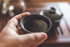 Male hand holds cup or piala or bowl of Chinese black tea, Chinese tea ceremony Stock Photo