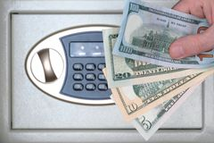 Male hand holds different US dollar banknotes against the background of a safe box. The concept of saving money, service in a. Male hand holds different US royalty free stock image