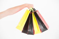Male hand holds five shopping bags. Shopping concept. Hand holds bunch of colorful shopping bags. Shopping on black. Friday. Client bought lot items with Royalty Free Stock Photography