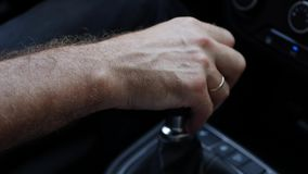 Male hand holds gear box. The driver switches the manual transmission in the car. Man rides by automobile. Closeup. Male hand holds gear box. The driver switches stock video footage