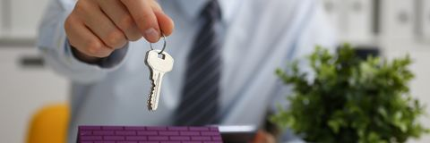 Male hand holds the key to the lock in the hand. Against the backdrop of the toy house sale purchase lease concept real estate services on the market Stock Photo