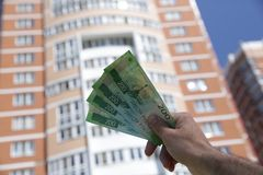Male hand holds a new Russian banknote two hundred rubles on the background of a big building and blue sky. Cash paper money royalty free stock photos