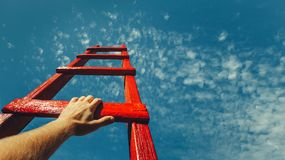 Development Attainment Motivation Career Growth Concept. Mans Hand Reaching For Red Ladder Leading To A Blue Sky. A male hand holds onto the crossbar of a red royalty free stock photos
