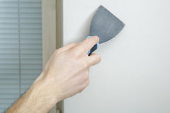 Male hand holds putty knife on the wall near the corner. Finishing work Stock Image