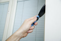 Male hand holds putty knife on the wall near the corner. Finishing work Royalty Free Stock Photos