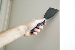Male hand holds putty knife on the wall near the corner. Finishing work Stock Photography