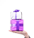 Male hand holds silver and purple gift Royalty Free Stock Photos