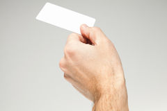 Male hand holds white card over gray Royalty Free Stock Photography