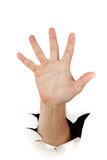 Male hand through a hole in paper Royalty Free Stock Image