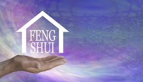 Feng Shui can work Wonders in your Home. Male hand with a house shape containing the words FENG SHUI floating above against a swishing lilac pink psychedelic stock photography