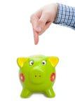 Male hand indicating on piggy bank - studio shot Stock Image