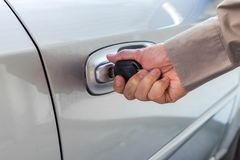 Hand opening car door with a key. stock photography