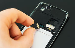 Male hand inserting Micro SD. Royalty Free Stock Photo