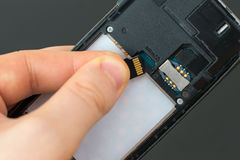 Male hand inserting Micro SD card. Royalty Free Stock Photos
