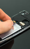 Male hand inserting Micro SD card. Stock Photo