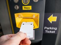 Male hand inserting parking ticket at electronic machine royalty free stock images