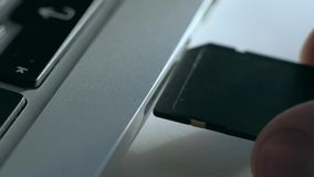 Inserts the SD card into the laptop. A male hand inserts a black compact SD card into the input in the side of the silver netbook. Man uses modern technologies stock video footage