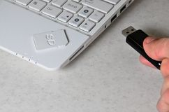 A male hand inserts a black compact USB card into the corresponding input in the side of the white netbook. Man uses modern techn. Ologies to store memory and stock photography