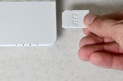 A male hand inserts a white compact SD card into the corresponding input in the side of the white netbook. Man uses modern techno. Logies to store memory and stock photography