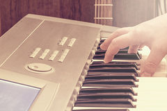 Male hand on the keyboard and guitar. Stock Photography