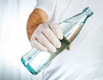 Male hand in latex glove holding glass bottle of water Royalty Free Stock Image