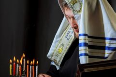 male hand lighting candles in menorah on table Hanukkah royalty free stock image