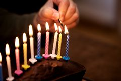 Male hand is lightning up some colorful candles. On a marble cake Stock Photos