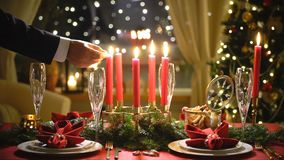 Male hand lights christmas candles. Festival red table setting with garland and Christmas tree in the background Slow motion stock video