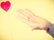 Male hand with little heart on stick. Stock Photos