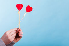 Male hand with little hearts on sticks. Royalty Free Stock Photos
