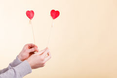 Male hand with little hearts on sticks. Stock Photo