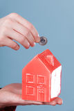 Male hand with little house and silver coin. Stock Photos