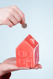 Male hand with little house and silver coin. Royalty Free Stock Photos