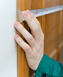 Male hand measuring door Royalty Free Stock Photo