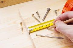 Male hand measuring wood flooring Stock Image