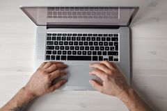 Male hand and a metal laptop on a white wooden table, top view. Male hand and a metal laptop on a white wooden table, top view Royalty Free Stock Photo