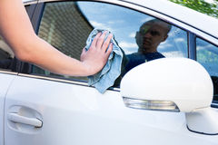 Male hand with microfiber cloth cleaning car. Male hand with blue microfiber cloth cleaning car Stock Image