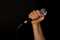 Male hand with microphone isolated on black Stock Images