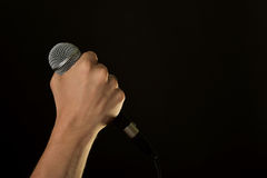 Male hand with microphone isolated on black. Male hand holding microphone with wire cable isolated on black background Stock Photos