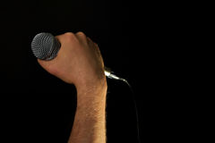 Male hand with microphone isolated on black. Male hand holding microphone with wire cable isolated on black background Royalty Free Stock Images