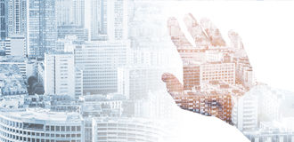 Male hand and modern big city background. Double exposure conceptual collage with a male hand and modern big city background royalty free stock photo